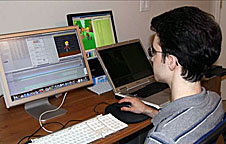 Kevin Temmer works with three computer monitors