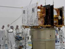 Technicians verify the GRAIL-A lunar probe is ready to be secured to the spacecraft adapter ring
