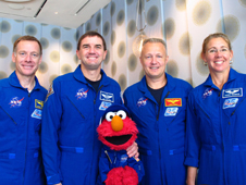 Sesame Street's Elmo poses with four astronauts