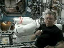 Astronaut Mike Fossum works on the Robonaut 2 helper droid.
