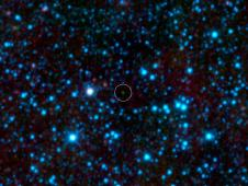 NASA's Wide-field Infrared Survey Explorer, or WISE, has uncovered the coldest brown dwarf known so far (green dot in very center of this infrared image)