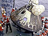 Ship's crew moving an Apollo capsule out of the water to the ship's deck