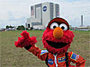 Sesame Street's Elmo stands in front of a large NASA buidling