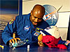 Sesame Street's Elmo watches Leland Melvin pour water on a piece of cloth
