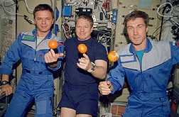 Picture of astronauts in space with oranges floating in front of them