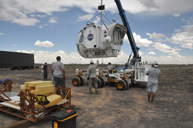 One of the Space Exploration Vehicle cabins is installed onto a Chariot chassis during the set up for the 2011 Desert RATS test.