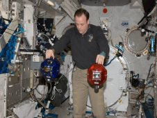 NASA astronaut Ron Garan, Expedition 28 flight engineer, performs a check on Synchronized Position Hold, Engage, Reorient, Experimental Satellites, or SPHERES, floating freely in the Kibo laboratory of the International Space Station.