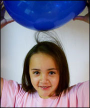 Photograph of balloon being rubbed on hair to create static electricity