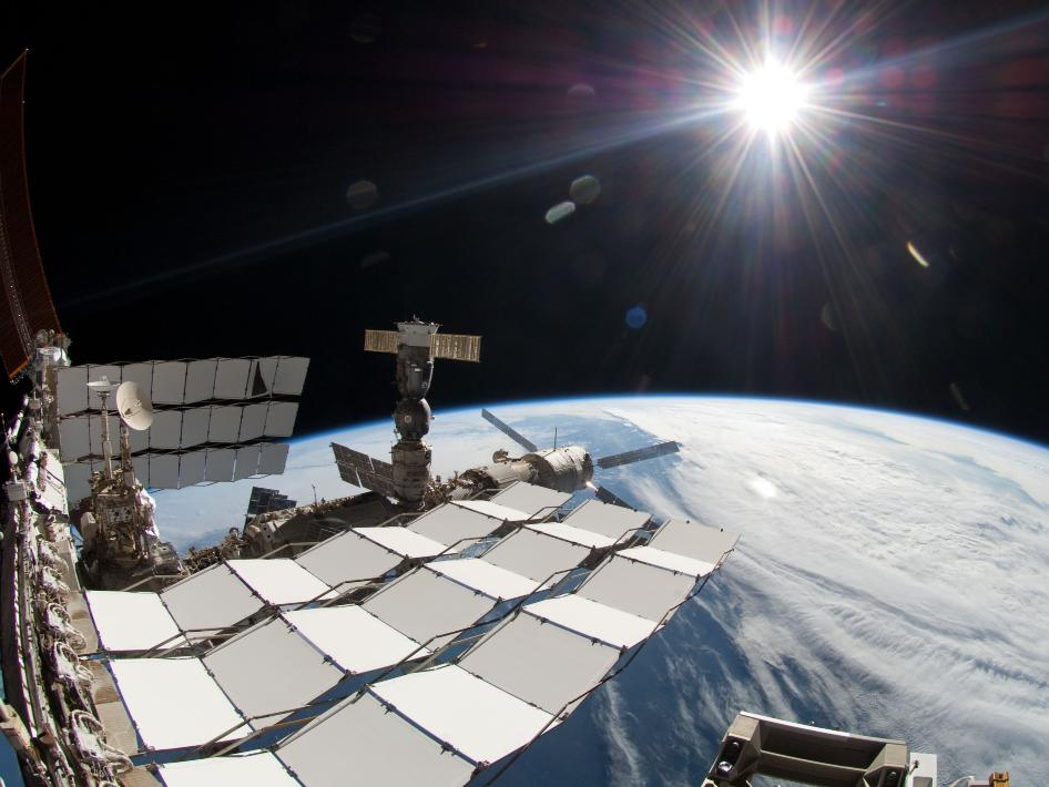 Bright sun, a portion of the International Space Station and Earth's horizon