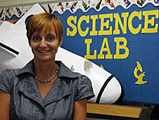 Teacher stands in front of a bulletin board with a 3-D space shuttle