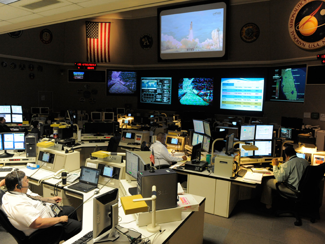 The communication networks team members sit on console in Goddard Space Flight Center's Networks Integration Center monitoring the communications link with the orbiter.