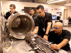 Research assistants in the Center for Space Exploration Technology Research prepare a microthruster test bed for integration into a vacuum chamber.