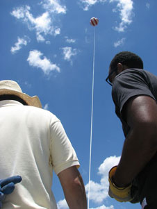 Summer intern John Moore and Dr. Jose Fuentes operate a winch to raise and lower the moored balloon carrying instruments to obtain profiles of meteorological variables and pollutants in the atmospheric boundary layer.
