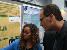 Ebony Daniels and Fernando Miralles-Wilhelm, URC director, discuss Ebony's research during the poster session at the end of summer internships at Goddard Space Flight Center.