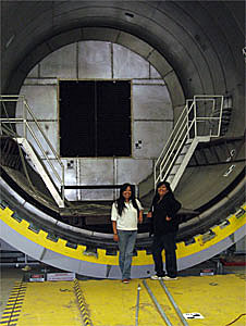 Two women standing in front of the 18-foot-wide opening of an autoclave