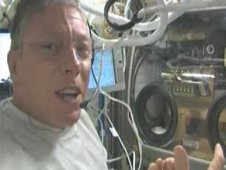Flight Engineer Mike Fossum aboard the International Space Station takes a moment to demonstrate the Shear History Extensional Rheology Experiment, or SHERE.