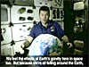 An astronaut on board the space shuttle floats with an inflatable ball that looks like Earth