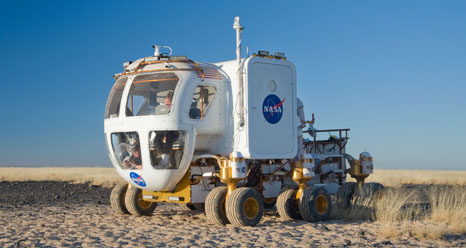 A space exploration vehicle is driven across a desert landscape