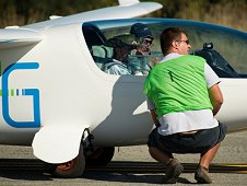 The e Genius pilots talk with a fellow team member prior to their takeoff for the miles per gallon flight during the 2011 Green Flight Challenge competition.