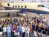 A large group of people stand in front of a research aircraft