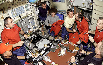Astronauts and cosmonauts share a meal aboard ISS.