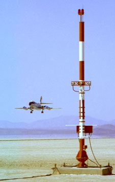 NASA Dryden's now-retired Lockheed JetStar flies a low landing approach to lakebed runway 35 at Edwards past the antenna of the space shuttle's microwave scanning beam landing system in 1977.
