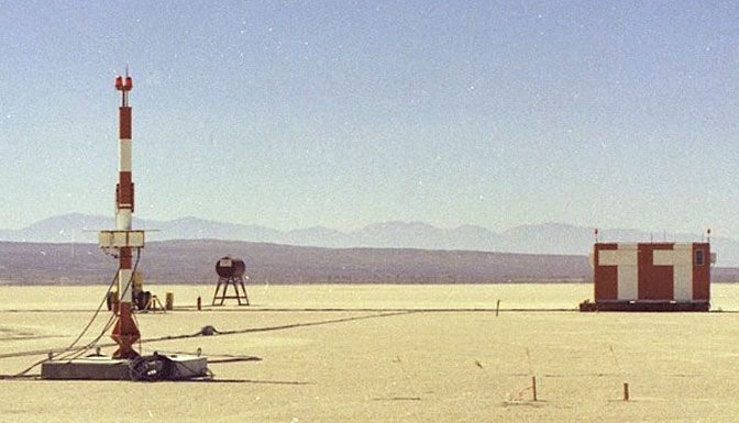 The primary ground-based components of the space shuttle MSBLS landing navigation system installed on the bed of Rogers Dry Lake at Edwards Air Force Base included the antenna at left and microwave scanning electronics in the orange and white structure at right.