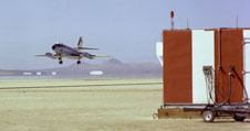 NASA Dryden's now-retired Lockheed JetStar flies a low landing approach to lakebed runway 17 at Edwards during checkout of the space shuttle's microwave scanning beam landing system housed in the enclosure at right.