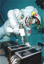 An astronaut practices drilling underwater