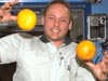Astronaut Edward M. (Mike) Fincke, Expedition 9 NASA ISS science officer and flight engineer, juggles fresh fruit in the Destiny laboratory. Photo credit: NASA/Johnson Space Center.