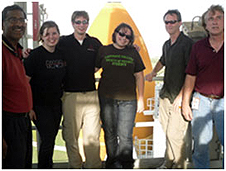 Six people stand in front of the space shuttle's external tank