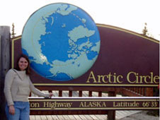 Erika Podest stands next to a sign marking the Arctic Circle