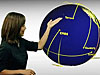 Woman stands beside drawing of Earth surrounded by satellites