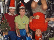 Astronauts on space station with Christmas hats and decorations
