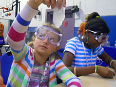 A girl wearing safety goggles holds up a large chunk of ice