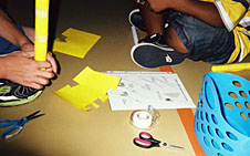 Two students sitting on the floor constructing a rocket with tape, colored paper and scissors
