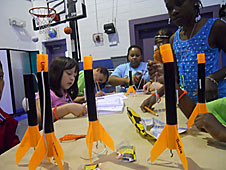 Orange and black model rockets sit on a table where students are seated