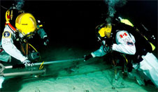 NEEMO 15 Commander Shannon Walker and crewmember David Saint-Jacques perform an EVA simulating small boom translation on an asteroid surface.