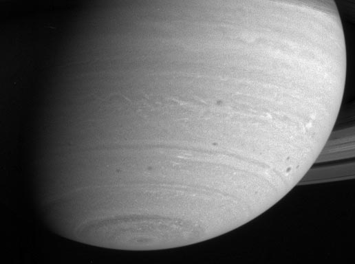 Saturn's southern hemisphere shows dark spots and wisps of high clouds