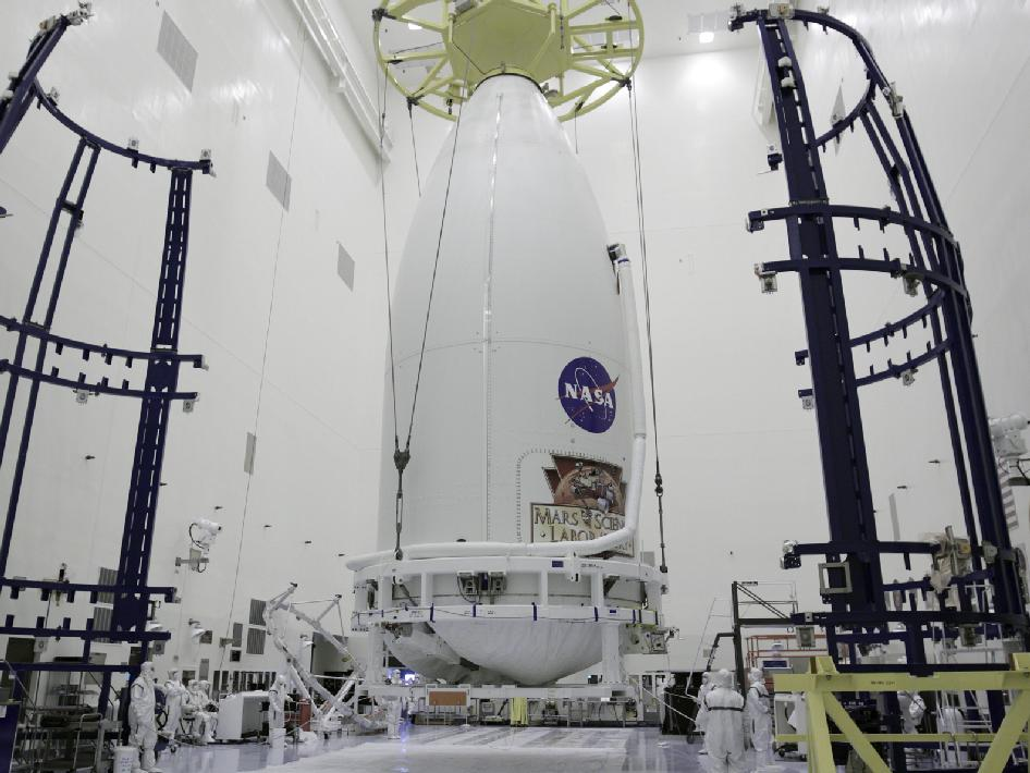 Technicians prepare to place the payload fairing containing MSL on a transporter