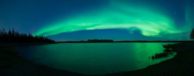 A picturesque lake reflects a beautiful green aurora in North Pole, Alaska.