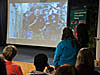 Students look at an astronaut projected on a large screen