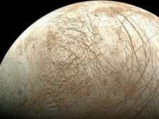 Europa, as viewed from NASA's Galileo spacecraft. Visible are plains of bright ice, cracks that run to the horizon, and dark patches that likely contain both ice and dirt. Image Credit: NASA