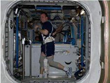 NASA astronaut Ron Garan, Expedition 27 flight engineer, equipped with a bungee harness, exercises on the Combined Operational Load Bearing External Resistance Treadmill (COLBERT) in the Tranquility node of the International Space Station