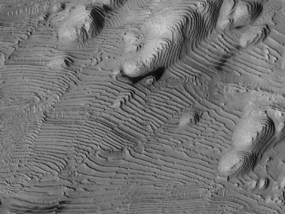 Rhtymic patterns of sedimentary layering in Danielson Crater on Mars result from periodic changes in climate related to changes in tilt of the planet.