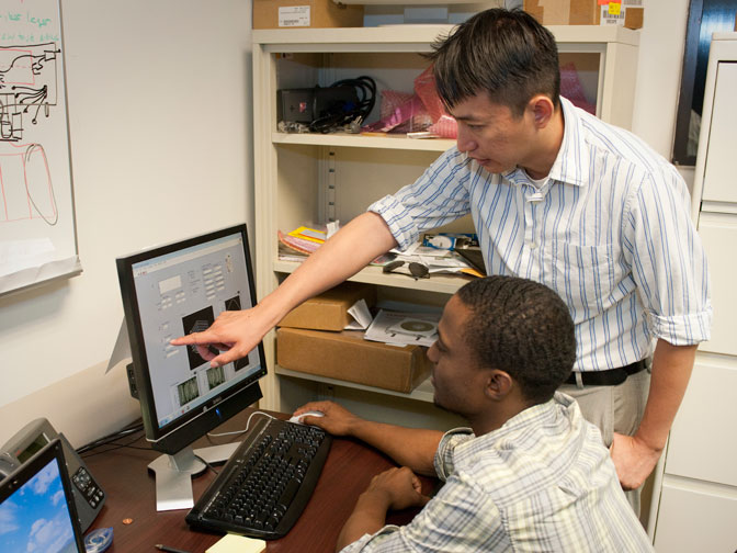 NASA summer intern Travis Withlow being instructed by Dr. Patrick Hon Man Chan on operating the software portion of the fiber optics strain sensing (FOSS) system.
