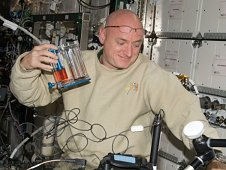 NASA astronaut Scott Kelly, Expedition 26 commander, works on the hardware setup for a Capillary Flow Experiment (CFE) Vane Gap-1 experiment.