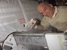 Astronaut Jeff Williams, Expedition 13 ISS Science Officer, places a POEMS sample into the MELFI freezer.