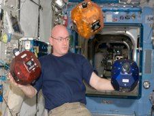 NASA astronaut Scott Kelly is pictured near three Synchronized Position Hold, Engage, Reorient, Experimental Satellites (SPHERES) floating freely in the Kibo laboratory of the International Space Station