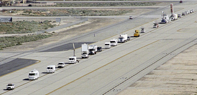 A long string of specialized NASA vehicles convoys down a taxiway at Edwards Air Force Base to begin a Space Shuttle rescue and recovery training exercise in April 2005